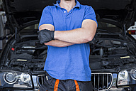 Mechanic standing in his car workshop with arms crossed - ABZF000969