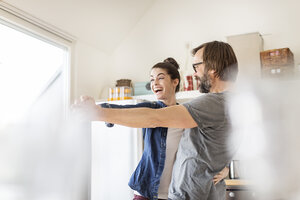 Playful couple dancing in kitchen - PESF000249
