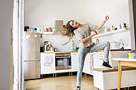 Playful young woman in kitchen - PESF000252