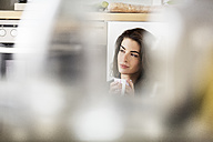 Young woman with cup of coffee relaxing in kitchen - PESF000261
