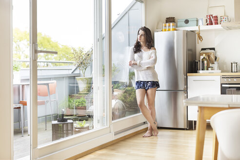 Young woman in kitchen looking out of balcony door - PESF000273