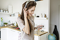Happy young woman in kitchen listening to music - PESF000279