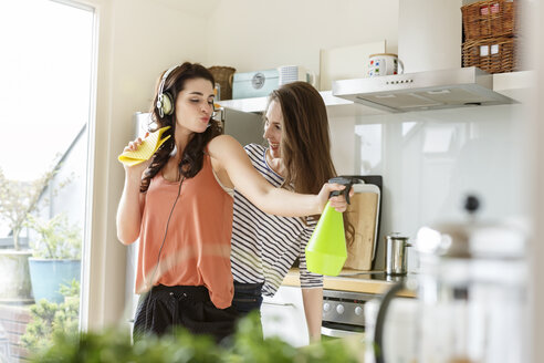 Two happy women in kitchen cleaning and listening to music - PESF000282