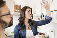 Sceptical woman in kitchen holding up glass - PESF000291