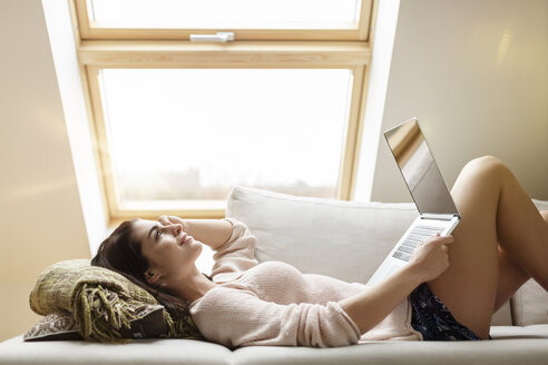 Relaxed woman lying on couch using laptop - PESF000297
