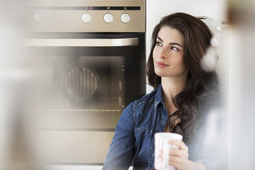 Young woman with cup of coffee relaxing in kitchen - PESF000309