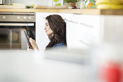 Young woman using digital tablet in kitchen - PESF000312