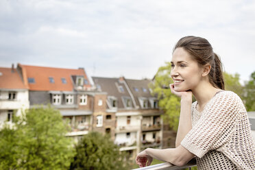 Smiling young woman standing on balcony - PESF000321