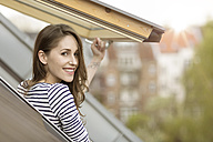 Smiling young woman looking out of roof window - PESF000333