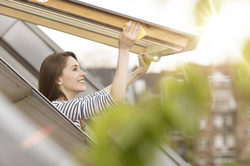 Smiling young woman cleaning roof window - PESF000336