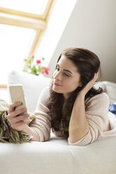 Relaxed woman lying on couch using cell phone - PESF000339