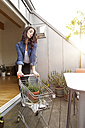 Young woman with potted plant in shopping cart on balcony - PESF000348