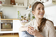 Happy young woman with cup of coffee in kitchen - PESF000351