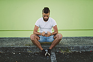Man sitting on his skateboard at carb text messaging - RAEF001367