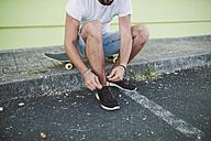 Skateboarder tying his shoe - RAEF001370