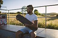 Skateboarder with his skateboard in a skatepark - RAEF001373