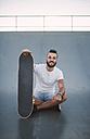 Smiling skateboarder sitting on ramp in a skatepark - RAEF001385