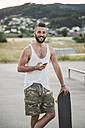 Portrait of smiling man with skateboard aand smartphone - RAEF001394