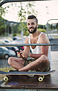 Portrait of smiling skateboarder with   smartphone - RAEF001400