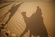 Shadows of people riding camels in the desert - KIJF000698