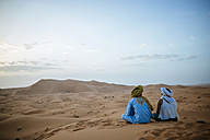 Woman sitting in the desert with Berber guide, watching sunset - KIJF000710