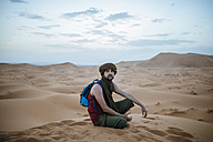 Tourist  wearing turban sitting in the desert - KIJF000713