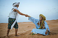 Woman helping her Berber guide to get up from the ground - KIJF000716