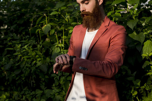 Fashionable young man with full beard checking the time - MAUF000722