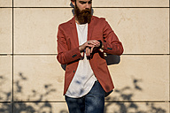 Fashionable young man with full beard checking the time - MAUF000725