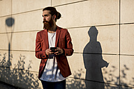 Fashionable young man with smartphone looking at distance - MAUF000728
