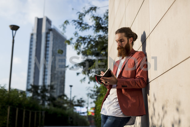 Fashionable young man with full  beard leaning against wall writing at his notebook - MAUF000731