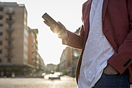 Young man with smartphone at backlight, partial view - MAUF000734