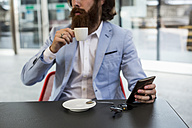 Stylish businessman holding cell phone in a cafe - MAUF000749