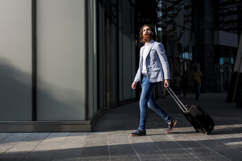 Stylish businessman walking with suitcase outdoors - MAUF000755
