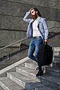 Stylish businessman walking with suitcase on stairs outdoors - MAUF000758
