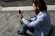 Stylish businessman using cell phone on stairs outdoors - MAUF000761