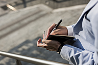 Businessman writing in diary outdoors - MAUF000764