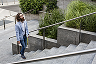 Stylish businessman walking on stairs outdoors - MAUF000773