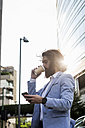 Stylish businessman with cell phone and coffee to go outdoors - MAUF000782