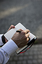 Businessman writing in diary outdoors - MAUF000791