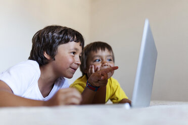 Two little boys lying on bed looking at laptop - VABF000734