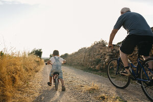 Back view of little boy and his great-grandfather on bicycle tour - JRFF000811