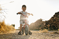 Little boy with children's bike on dirt track - JRFF000814