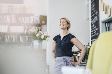 Smiling woman in a cafe - KNSF000227