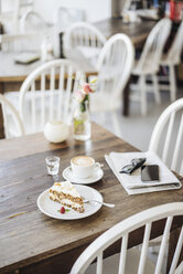 Cell phone, sunglasses, cake and cup of coffee on table in a cafe - KNSF000230