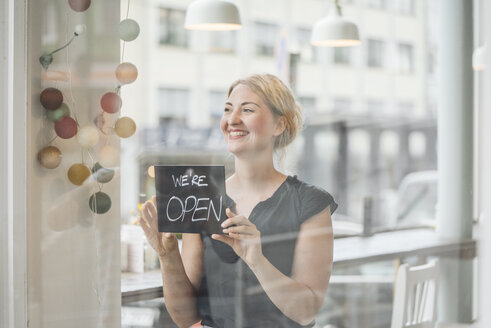 Smiling woman in a cafe attaching open sign to glass pane - KNSF000233