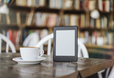 E-book and cup of coffee on table in a cafe - KNSF000236