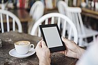 Man holding e-book in a cafe - KNSF000239