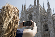 Italy, Milan, back view of tourist taking picture of cathedral with cell phone - MAUF000798