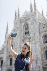 Italy, Milan, tourist taking selfie with cell phone in front of cathedral - MAUF000801